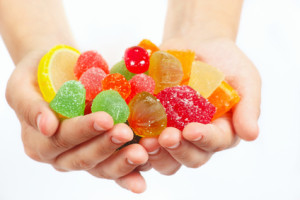 Child hands with colorful sweetmeats and jelly closeup