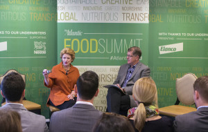 Stabenow demonstrating the half-cup fruit and vegetable requirement at The Atlantic's Food Summit, October, 2015 in Washington, DC. (Also on stage: Steve Clemons of The Atlantic)